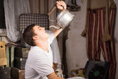 Young Man Drinking Something From Vintage Kettle — Stock Photo