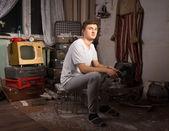 Sitting Man at the Junk Room Looking at Camera — Stock Photo