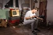 Sitting Man Holding Unused Kettle at Junk Room — Stock Photo