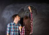 Young Couple in Front Black Chalkboard — Stok fotoğraf