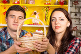Smiling couple holding a wicker basket of cookies — Stock Photo