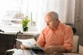 Sitting Pensioner Reading News on Tabloid — Stock Photo