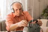 Sitting Old Man Listening News at the Radio — Stock Photo