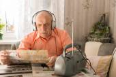 Old Man Listening From radio While Reading Tabloid — Stock Photo
