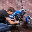 Sitting Young Guy Repairing his Motorcycle — Stock Photo #67830959