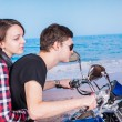 Постер, плакат: Lovers Riding a Motorbike at the Tranquil Beach
