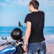 Man with Motorcycle Looking into Distance on Beach — Stock Photo #67831375