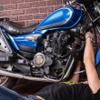 Lying Young Guy Fixing his Sports Motorbike — Stock Photo #67831567