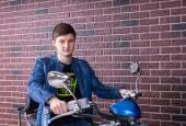 Zamyślony młody motocyklista czeka na rowerze — Zdjęcie stockowe
