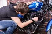 Young man tinkering with his motorbike — Stock Photo