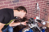 Young Man Closely Examining Gauges on Motorcycle — Stock Photo