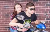 Young Couple on Motorcycle in front of Brick Wall — Stock Photo