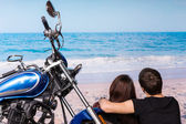 Romantic couple at the beach with their motorbike — Stock Photo