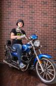 Portrait of Young Man on Motorcycle by Brick Wall — Fotografia Stock