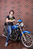 Young Man on Motorcycle in front of Brick Wall — Fotografia Stock