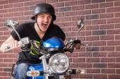 Enthusiastic young man riding his motorbike — Stock Photo