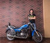 Young Man Standing Beside Motorcycle Against Wall — Stock Photo