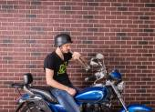 Young man sitting drinking alcohol on his bike — Stock Photo