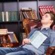 Tired young man dozing off in the library — Stock Photo #68607121