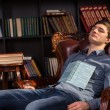 Attractive young man asleep in a library — Stok fotoğraf #68607129