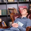 Tired young man asleep in the library — Stok fotoğraf #68607133