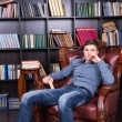 Handsome Young Guy Sitting on the Library Chair — Stock Photo #68607225