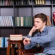 Handsome Guy at the Library Looking at his Watch — Stock Photo #68607251