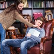 Librarian trying to wake a sleeping man — Stock Photo #68607291