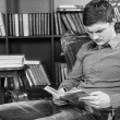 Serious Young Man Sitting on a Chair Reading Book — Stok fotoğraf #68608073
