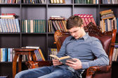 Young man sitting reading in the library — Stock Photo