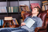 Tired young man dozing off in the library — Stock Photo