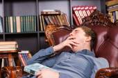 Sleepy young man yawns as he relaxes in a library — Stock Photo