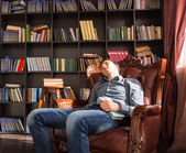 Young man dozing off in a public library — Stock Photo