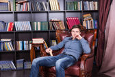Handsome Young Guy Sitting on the Library Chair — Stock Photo