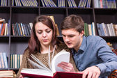 Young couple paging through a book in the library — Photo