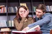 Happy Young Lovers Reading a Book at the Library — Stock Photo