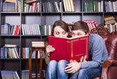 Lovers Hiding Behind a Book Looking Each Other — Stock Photo