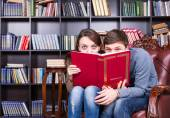 Sweet Couple at the Library Hiding Behind a Book — Stock Photo