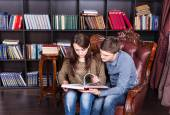Serious Young Couple on a Chair Reading a Book — Stock Photo