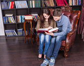 Young Couple Sitting at the Library Reading a Book — Stock Photo