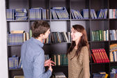 Happy Young Couple Talking Inside the Library — Stock Photo