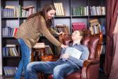 Librarian waking a sleeping man in the library — Stock Photo