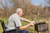 Old Man on Wheelchair Grilling Sausage Outsides — Stock Photo
