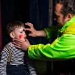 Man Applying Clown Make Up to Boys Face — Stock Photo #72162979
