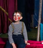 Happy boy with clown make up sitting on a stage — Stock Photo