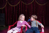 Boy and Girl Clowns Sitting in Chairs on Stage — Stock Photo