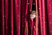 Impatient young actor peeking out from the curtain — Stock Photo