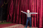 Laughing confident little boy on stage — Stock Photo