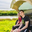Couple Sitting on Tailgate of Car near River — Stock Photo #73877111