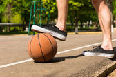 Close Up of Man with Foot on Basketball on Court — Stock Photo